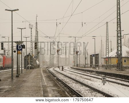 Freilassing,Germany-Marcch 15,2016: View of  railroad tracks at a train station during snowfall