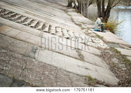GOMEL BELARUS - MARCH 29 2017: an unfamiliar man is fishing on the embankment of the city