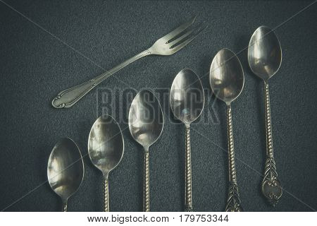 Vintage silver tea spoons on a gray background