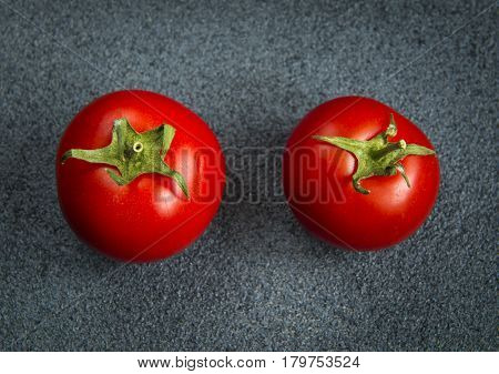 Two tomatoes on a dark gray background