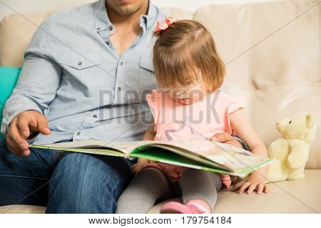 Pretty Little Girl Reading With Her Father