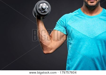 A closeup look of a young sportsman lifting a dumbbell with one hand
