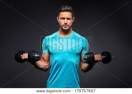 A handsome young sportsman lifting a dumbbells with both of his hands