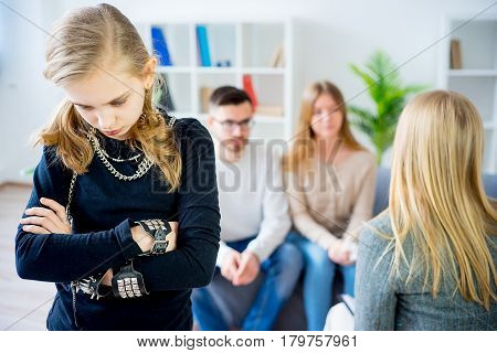 Teenage girl during therapy session while therapist is taking notes