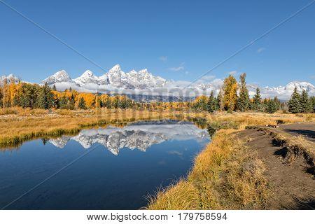 the scenic Teton range in Wyoming reflected in fall