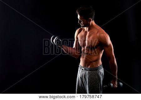 A half naked handsome young sportsman lifting dumbbells