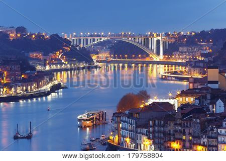 Picturesque aerial view of Old town of Porto, Ribeira and bridge with mirror reflections in the Douro River during evening blue hour, Portugal