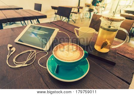hot coffee and a pot of tea on wooden table with computer tablet and earphone in a hip and relax coffee shop vintage color tone