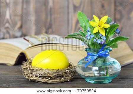 Easter card with yellow Easter egg and spring flowers