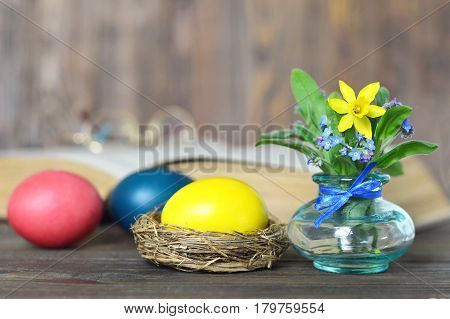 Easter eggs, spring flowers and old book on wooden background