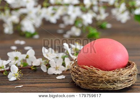 Happy Easter card with Easter egg in the nest and spring flowers