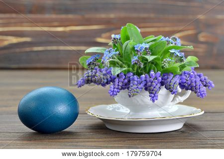 Easter card with Easter egg and spring flowers in tea cup