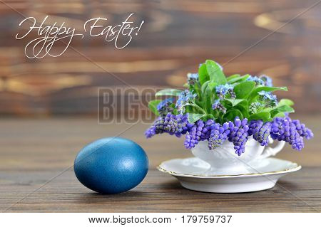 Happy Easter card with Easter egg and spring flowers in tea cup