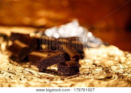 Tasty porous black chocolate pieces on a gold foil