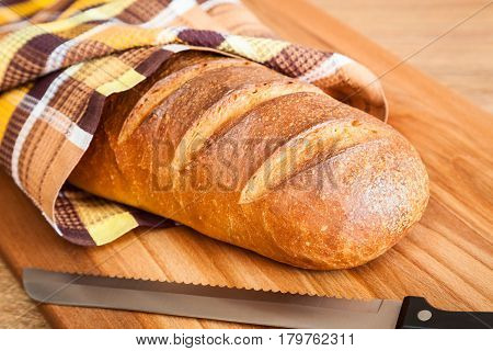 Traditional Russian wheat bread and bread knife on a cutting board closeup