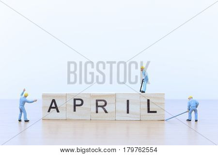 April words with Miniature people worker on wooden floor