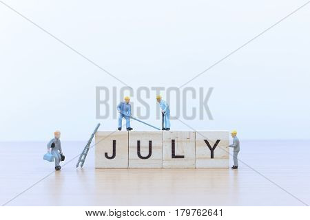 July words with Miniature people worker on wooden floor