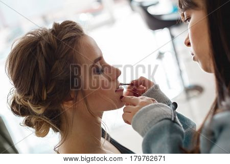 Kyiv, Ukraine - March 3, 2017: Young beautiful girl applying makeup by make-up artist. Young beautiful bride applying wedding make up.