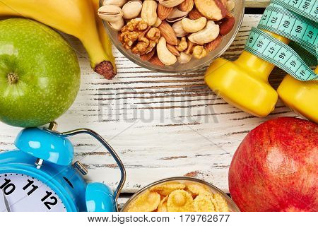 Alarm clock, fruits and nuts. The rules of being healthy.