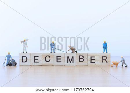 December words with Miniature people worker on wooden floor