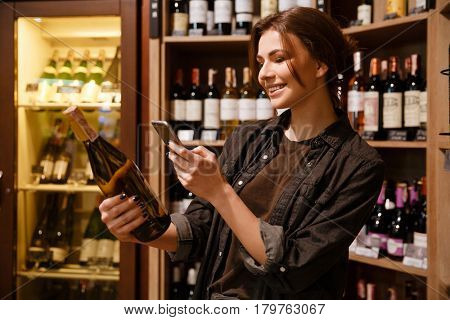 Image of happy young woman choosing vine and scanning bar code on the bottle in grocery store