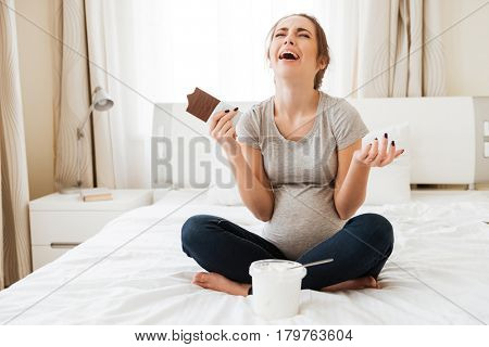 Stressed offended pregnant young woman crying and eating chocolate with ice cream on bed