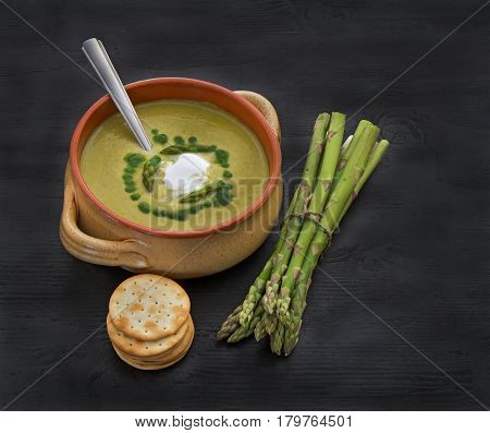 Cream of asparagus soup crackers and bunch of fresh asparagus on dark wooden background