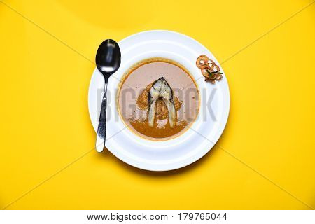 Cream Soup Brown Color With Fish And Fried Onion Rings