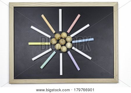 Black chalkboard with colored chalks forming a circle and wooden balls in the center