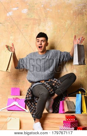 handsome man young caucasian guy with surprised happy face near fashionable hangers and colorful shopping bag or present package and gift boxes in sweater sitting on wooden stairs on beige background