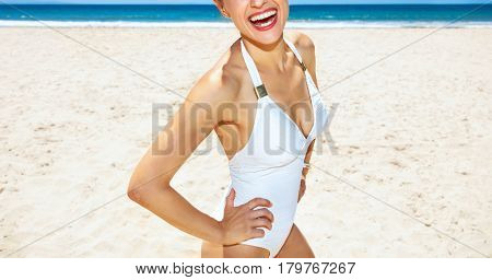Closeup On Smiling Woman In White Swimsuit At Sandy Beach