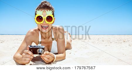 Smiling Woman In Pineapple Glasses With Photo Camera At Beach