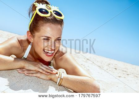 Smiling Woman In Swimsuit And Pineapple Glasses Laying On Beach