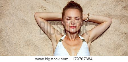 Portrait Of Relaxed Woman In Swimsuit Laying On The Sand