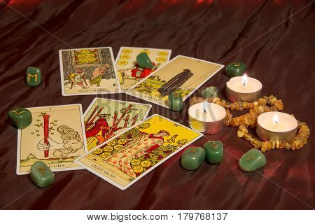 Moscow Russia - December 4 2016: Rider-Waite tarot cards with runes and burning candle. Esoteric background.