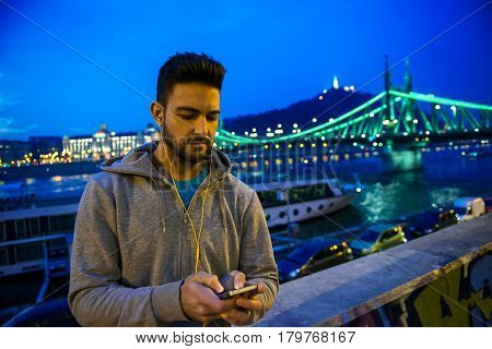 A handsome young sportsman using his phone while standing in the city lights on the riverside at night