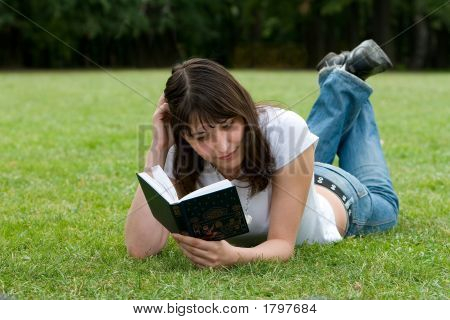 A Girl Reading A Book On Meadow