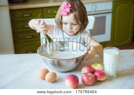 A child cooks in the kitchen. The concept of education family cooking