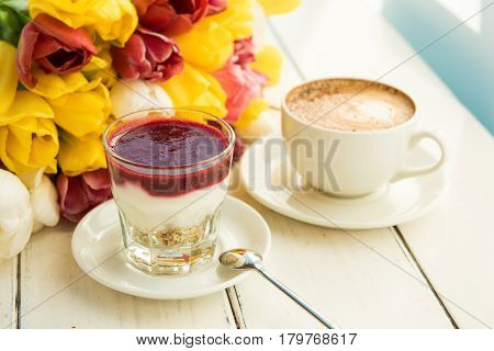 Couple: yogurt and coffee on the table. Background of red yellow and white flowers
