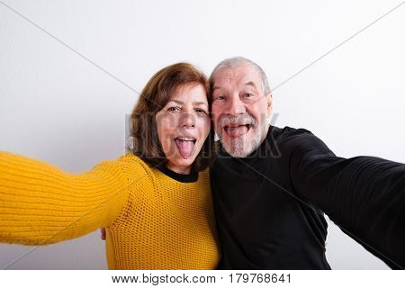 Beautiful senior couple making funny faces, sticking tongues out, taking selfie. Studio shot against white wall.