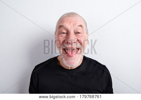 Handsome senior man in black t-shirt, making funny face, sticking tongue out. Studio shot against white wall.