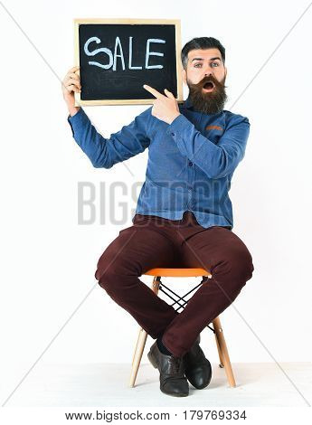 Bearded man long beard. Brutal caucasian surprised hipster with moustache holding sale inscription on blackboard sitting on orange chair wearing blue shirt vinous pants isolated on white background