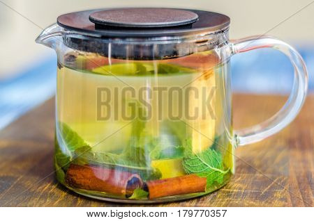Glass teapot with black tea. Ginger tea with lemon and cinnamon on a wooden board