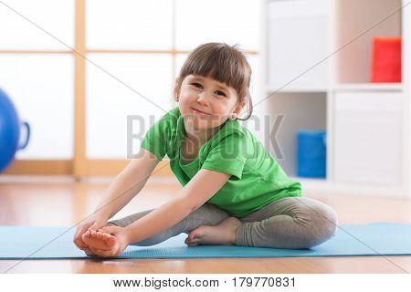 Little girl doing fitness exercises in nursery room