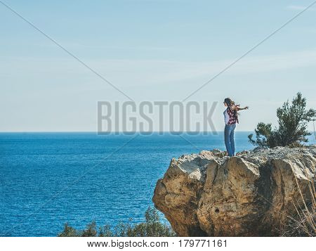 Young happy black haired girl traveler in checkered shirt standing on rock over the sea in Mediterranean region of Turkey, Alanya, on sunny clear day, copy space. Traveling, freedom concept