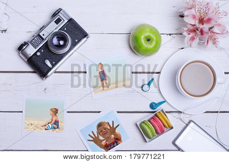 Old photo camera smartphone headset and cup of coffee on a wooden background. The concept of summer holidays family photos.