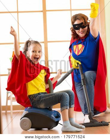 Kid and mother dressed as superheroes using vacuum cleaner in room. Family middle-aged woman and kid daughter have a fun while cleaning the floor.