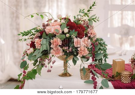 Wedding table decoration with the red and pink bouquet on the white cloth