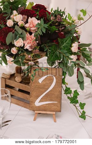 Wedding table decoration with the red and pink flowers and wooden box on the white cloth