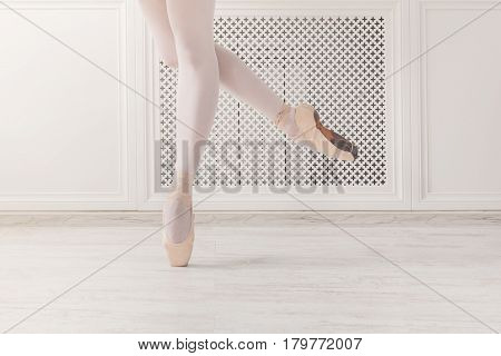 Ballerina legs dance, stand on pointe shoes at white wooden floor background, with copy space. Ballet practice. Beautiful slim graceful feet of ballet dancer.